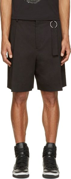 Pleated wide-leg cotton twill shorts in black. Four-pocket styling. Key-ring with textile strap at front belt loop. Tonal stitching. Zip-fly.