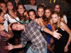 A college party where a man is saying with girls in the background.