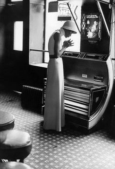 1972, Halston in Harlem - Naomi Sims choosing a song from the jukebox at Harlem's Lucky Spot Restaurant, photo by Berry Berenson