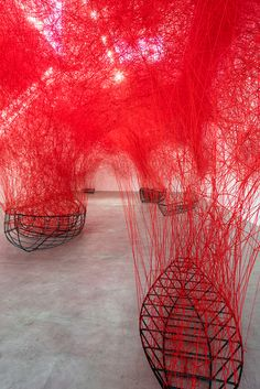 chiharu-shiota-uncertain-journey-blain-southern-designboom-02 complex mesh labyrinth reaches down towards a series ofl boat hulls. the red color symbolises the interior of the body,thread strands refer to the neural connections in the brain. the boats intend to raise existential questions of fate and belonging - migrations