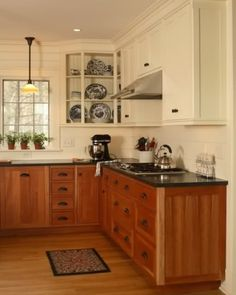 Wood lower cabinets, white upper, black countertop.