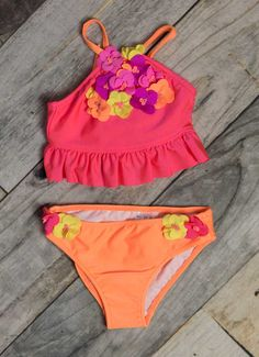 Bright, vivid and full of color this shimmery girls swimsuit is a fantastic choice for a day in the water.  A tropical swimsuit for infant, toddler and little girls features a two piece design with a bright coral pink top with a bunch of colorful attached flowers and ruffled hemline.  Included matching swim bottoms in an eye catching orange with attached flowers at the hip makes sure this little girls tropical swimsuit is one you'll never forget!