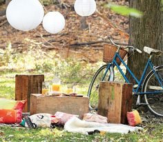 Backyard picnic with bike, crates, blankets, cider, glass jars