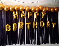 Happy Birthday Balloons taped on a backdrop of black streamers with gold…