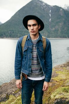 Shop this look for $131:  http://lookastic.com/men/looks/jeans-and-denim-jacket-and-crew-neck-sweater-and-crew-neck-t-shirt-and-hat/1281  — Navy Jeans  — Navy Denim Jacket  — Grey Fair Isle Crew-neck Sweater  — White Crew-neck T-shirt  — Black Hat