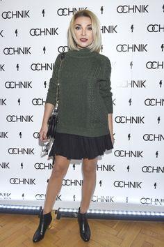 Katarzyna Krupa ubrana w grafitowy, gruby sweter i czarną spódniczkę mini plisowaną.