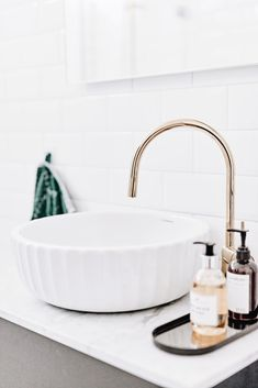 White bath sink with gold faucet, white bath cabinet top and white subway tiles.