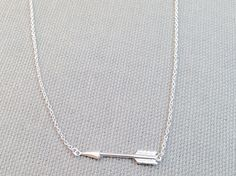 Silver Arrow Necklace. Arrows are awesome. They look cool, they symbolize direction and leading, and they have been used for thousands of years by all kinds of people and cultures. This necklace encompasses all awesomeness of the afore mentioned things. This lovely sterling silver necklace is 16 inches long with a 2 inch extension with white bead charm on the end and lobster clasp closure.