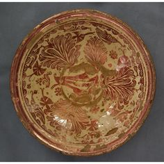 Antique 17th century large Hispano-Moresque copper lustre conical ceramic bowl, with deeply sloping sides, with a banded rim decorated on the center with a stylized bird among carnations and scattered flowers, within a border of concentric bands, and scroll-pattern.