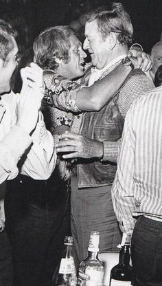 Steve McQueen hugging John Wayne     On close inspection it appears Steve's about two sheets to the wind and has just knocked off the Duke's custom Stetson. The Duke don't care, he loves him anyway.