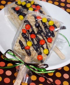 rice krispies on a stick with reeses pieces and and a chocolate drizzle.... cute!