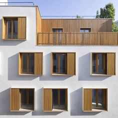 French studio Explorations Architecture have completed a social housing block beside one of the narrowest streets in Paris. The five-storey building provides eighteen apartments in a rundown neighbourhood in the centre of the city. Timber box-frame windows are staggered across a white stucco exterior to maximise natural light into each flat. Timber-lined balconies occupy recesses