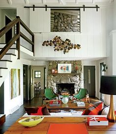 statement art, green chairs, modern cabin, rock fireplace