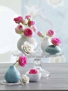 In Weiß, Blau und Rosa auf mehreren Ebenen verteilt stehlen die Vasen und Rosen jedem Accessoire die Schau.