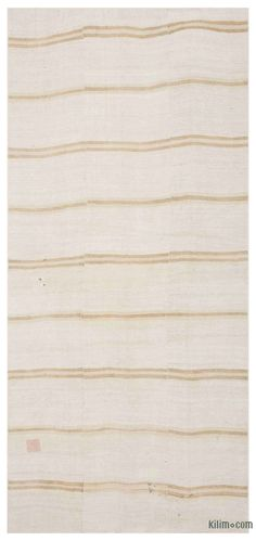 Vintage kilim rug handwoven in Turkey with hemp fiber. Turkish villagers produced hemp stalk until the 1960's when its production was prohibited together with its cousin, medical cannabis. These Anatolian rugs with modern appeal were mostly woven for drying fruits, to store wheat or as floor covers. This minimalistic beige rug measures 5'4'' x 11'10'' (64 in. x 142 in.).We professionally clean all our vintage rugs, but stains are a reminder of the rugs' history.