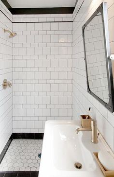 Black and white bathroom boasts a black rivet industrial mirror, Restoration Hardware Industrial Rivet Flat Mirror Pivot, placed over a white porcelain sink and gold faucet.