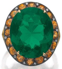 A very fine emerald, spessartite garnet and diamond ring  Centring on an oval emerald weighing 12.52 carats, within a border of circular-cut spessartite garnets and single-cut diamonds, size 53. Sotheby's.