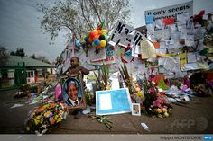 SOUTH AFRICA, Pretoria: A child stands with a Nelson Mandelas portrait outside the Medi Clinic Heart hospital where former South African president Nelson Mandela lays in critical condition in Pretoria on July 6, 2013. Emotional crowds gathered outside the hospital, as relatives and clan elders made preparations for the revered former South African leaders final journey. AFP PHOTO / Filippo MONTEFORTE