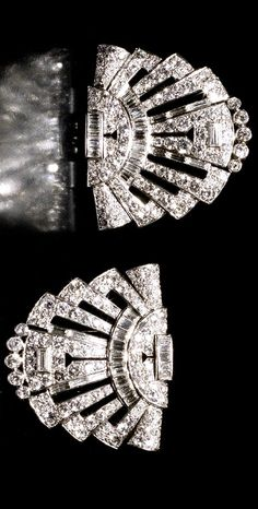 A pair of art deco diamond clip brooches, circa 1930 Each openwork clip of radiating fan design, set throughout with brilliant, baguette and single-cut diamonds, mounted in platinum, diamonds approximately 6.80 carats total, length of each 3.2cm, fitted case by Cartier