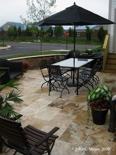 An outdoor room created with a ScabosTravertine patio and a small waterfeature built into the wall.