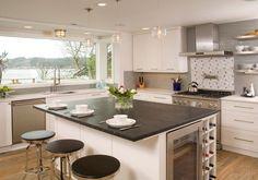 Dieser weiß lackiert Kücheninsel mit einem Weinkühler und Wein rack mit schwarzer Keramik Arbeitsplatte und Frühstück Zähler die beste Position hat für den Genuss der vollen Fenster mit Blick auf die verlockende im Freien.