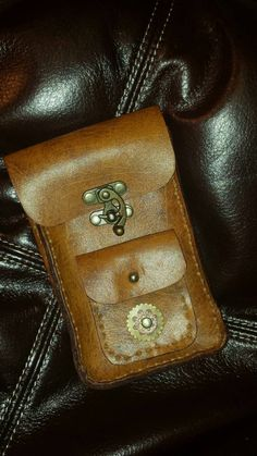Steampunk pouch or cellphone case. Real leather hand-sewn construction with a swing style clasp for that classy Victorian look. Has handy metal ring and belt loop for easy attachment. Can be customized to fit your phone. Custom orders will take longer to produce.