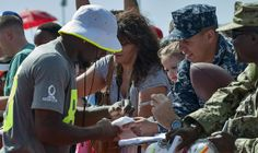 140123-N-XD424-039 PEARL HARBOR (Jan. 23, 2014) Dallas Cowboy wide receiver Dez Bryant signs autographs for service members and their families at Earhart Field on Joint Base Pearl Harbor-Hickam. Players from the National Football League (NFL) are in Hawaii for the 2014 Pro Browl at Aloha Stadium. (U.S. Navy photo by Mass Communication Specialist 2nd Class Dustin W. Sisco/Released)