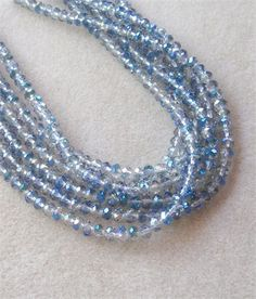Clear Faceted Glass Beads with AB Blue Finish, Crystal Glass Beads, Jewelry Making Beads, Craft Supply, Bead Supply Jewelry Supplies, (1)    In this listing are clear faceted rondelle beads with a blue AB finish. They are really pretty, sparkly beads and will make your jewelry designs pop! Each purchase is for 1 full bead strand that is 14 long with about 76 beads that are 5 x 6mm in size. Must see to appreciate!    Each strand is randomly selected from the group shown.   All sizes are…