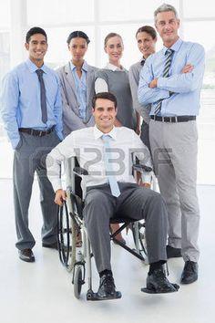 silla de ruedas: Hombre de negocios en silla de ruedas con sus colegas mirando a la cámara en la oficina