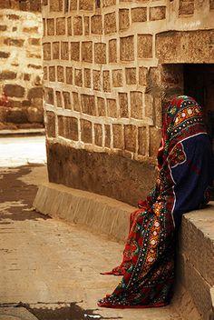 Yemen | A woman draped in a vivid sitarah resting in Sanaa | ©Anthony Asael