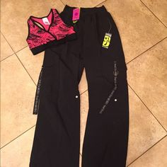 Zumba NWT bundle of 2 size S/M. #806 NWT bundle includes a race back sports bra size S (fits 4-6) A pair of cargo pants with graphic and hardware detail on pockets size M. Tags attached no flaws Zumba Other