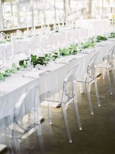 white table linens paired with leafy green centrepiece garland on long dining tables http://www.himisspuff.com/acrylic-and-lucite-wedding-decor-ideas/7/paired with clear acrylic ghost chairs