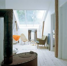 I dream of having a room like this. Giant skylight. Indoor hammock. Wood stove. Bare wood floors. All good.