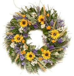 wreath with life-like mini silk sunflowers, purple and white statice, lavender larkspur, golden yellow yarrow, basil green eucalyptus, bear grass and salal.