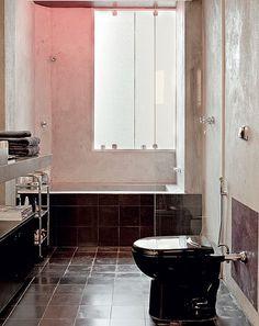 O designer de interiores Sandro Brasil economizou nos acabamentos de seu apartamento, mas criou efeitos de iluminação diferentes. A banheira de alvenaria com cimento queimado tem lâmpadas vermelhas, que transformam o banho em sessão de cromoterapia