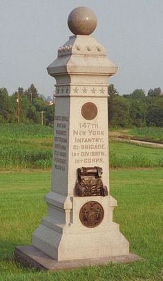 Monument to the 147th New York Infantry at Gettysburg,  with the Railroad Cut through Seminary Ridge in the background.