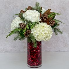 Yuletide: This elegant tall glass cylinder is chuck full of fresh cranberries, fragrant fir, cedar, magnolia and white hydrangea accented with natural pinecones. A classic traditional Christmas arrangement perfect for the big day or any winter celebration.