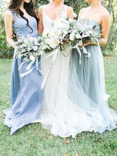 Bride with bridesmaids in blue dresses. Bouquets of white and gray flowers by Petal Flower Company, dresses by BHLDN. Image by Rachel May Photography.