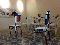 Cadiras ( sedie)  di Consuelo Mele ( Galtellì).  Sullo sfondo, grafico su pannello di Tela Urbana ( Nuoro, collettivo di writers).