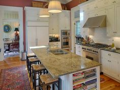 tall cupboards, granite island with rush seat stools, oriental runners