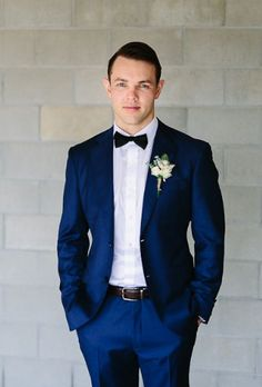Dark navy blue suit + gray or silver bowtie with pink flower