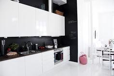 love this ... black splashback, white cabinetry, no handles, white tiled floor. chalkboard.