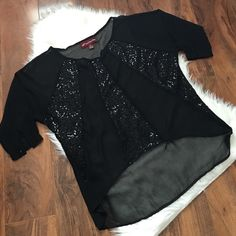 Black blouse w/sequin detail Cropped in the front, with sequin detail. Buttons on sleeves. Over all good condition. Offers welcome through offer tab. No trades. Sugar & spice Tops Blouses