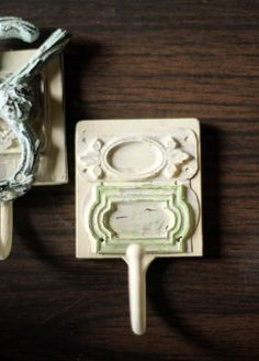 Shabby Chic Hooks: Buy plastic hooks from the dollar store and stick faux metal embellishment tags on them. Then paint them with some acrylic paint, and you have your shabby chic hooks!