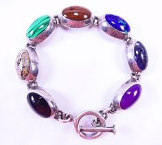 SoVintageous is offering this gorgeous handmade Taxco, Mexican multi-gemstone sterling silver bracelet.  In excellent vintage condition, the bracelet consists of 7 natural gemstones inlaid in sterling