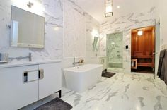 This NYC bathroom has marble paneled floors and ceilings, a wooden steam room, glass enclosed shower, stand-alone tub, white cabinet, plush area rug, and hanging lantern fixture.