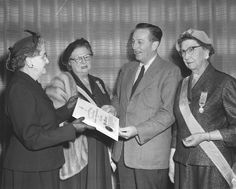 """Photograph caption reads: """"Walt Disney receives citation from Mrs. William A. Pollard on behalf of the California Socity, Daughters of the American Colonists, for his """"true patriotism and loyalty to the United States."""" Looking on are, from left, Mrs. H. H. Dace and Mrs. Roscoe M. Breeden"""". Photograph dated: March 14, 1955."""