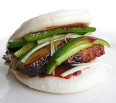 Gua bao ideetjes :: Gua bao besmeerd met hoisinsaus, daarop Momofuku's buikspek, lente-uitjes, ingelegde komkommer en sriracha.