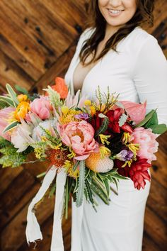 This bride contrasted her simple long-sleeved wedding dress with a beautiful colorful wedding bouquet filled with peonies, anthuriums, ranunculi, and mums. All the colors from pink peonies to the orange mums are perfect for a glamorous spring or summer wedding. Click for more peony filled bouquets! // Photo: Plum & Oak Photography