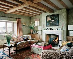 class trad English sitting room ... comfy furniture, built-in storage cabinets flank fireplace, mix of textiles and Oriental carpets, William Morris willow pattern wallpaper